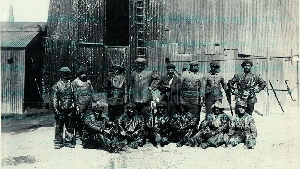 Operarios y jefe posando frente a una torre de petróleo. (Archivo Histórico Museo Nacional del Petróleo)