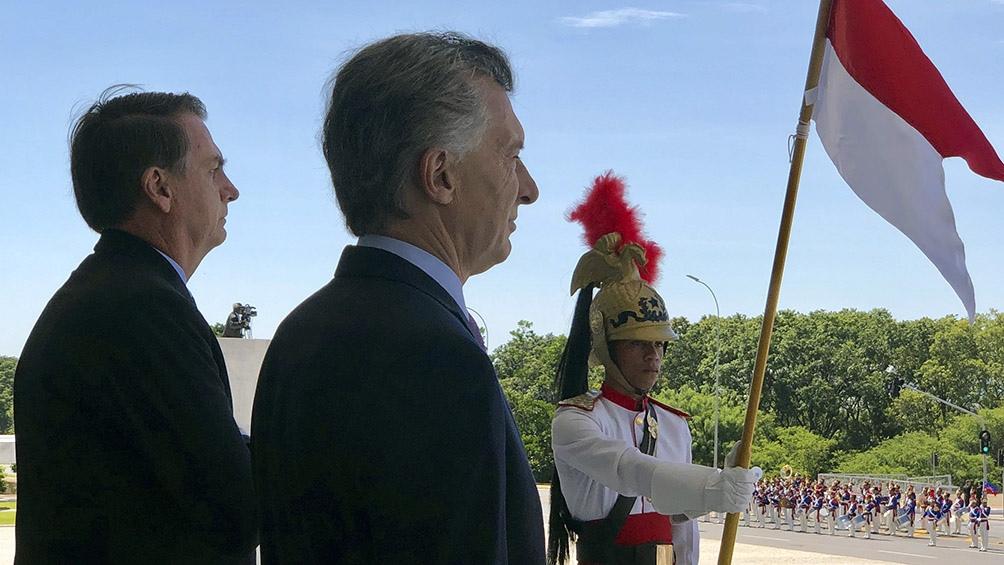 Bolsonaro y Macri escuchan los himnos de sus respectivos países.