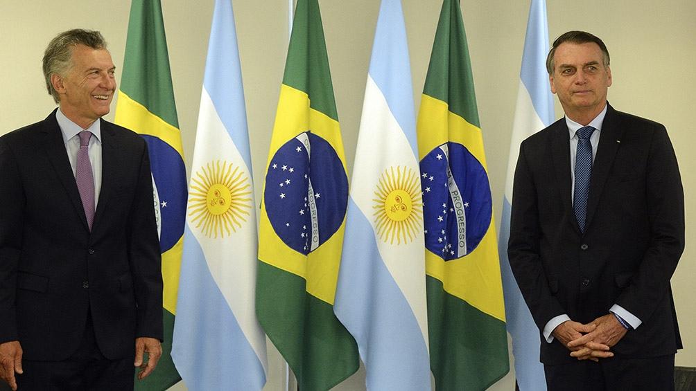 Los presidentes posan frente a las banderas de sus países.