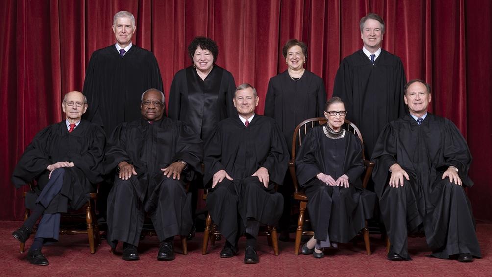Fila de adelante, de izquierda a derecha: Juez Asociado Stephen G. Breyer, Juez Asociado Clarence Thomas, Juez Presidente John G. Roberts, Jr., Juez Asociado Ruth Bader Ginsburg, Juez Asociado Samuel A. Alito. Fila posterior: Juez asociado Neil M. Gorsuch