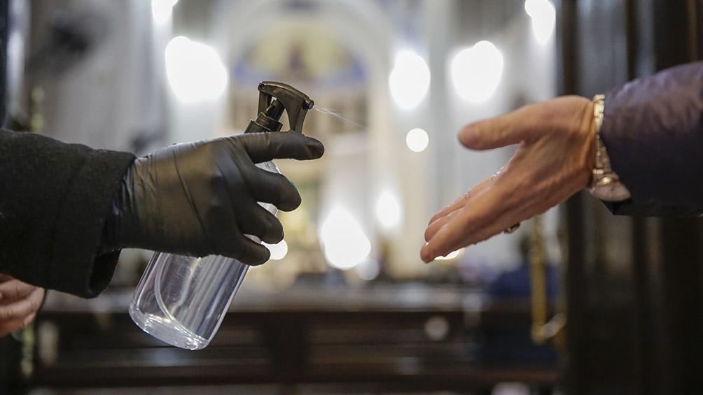 Un voluntario espera a los fieles en el ingreso para que se cumplan los pasos de higiene