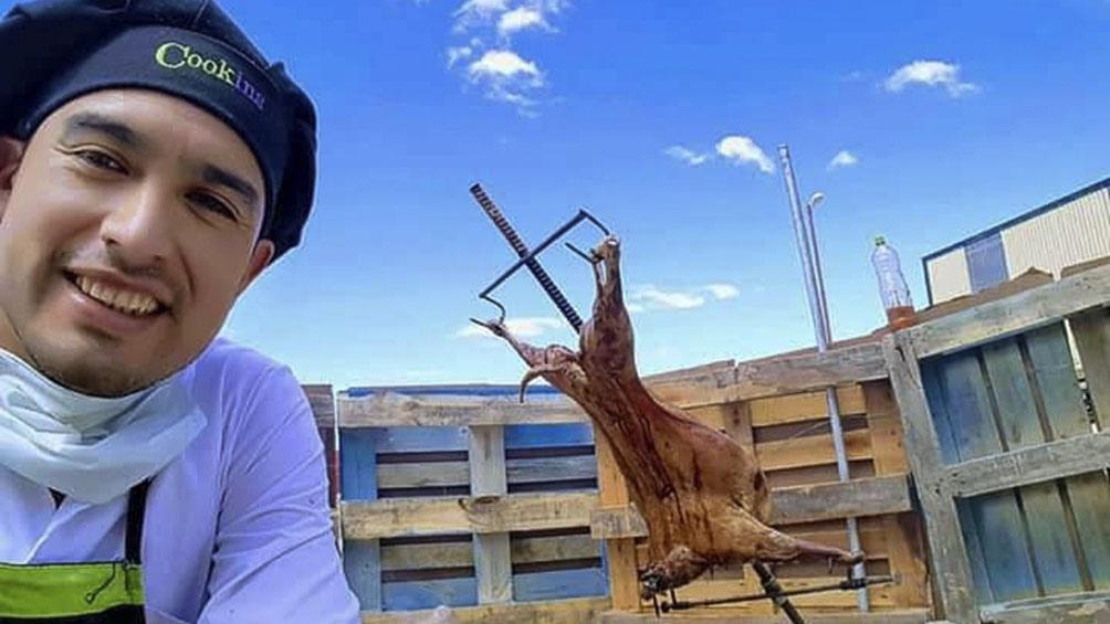 Cristian Gauna y un típico cordero patagónico asado en la cruz.