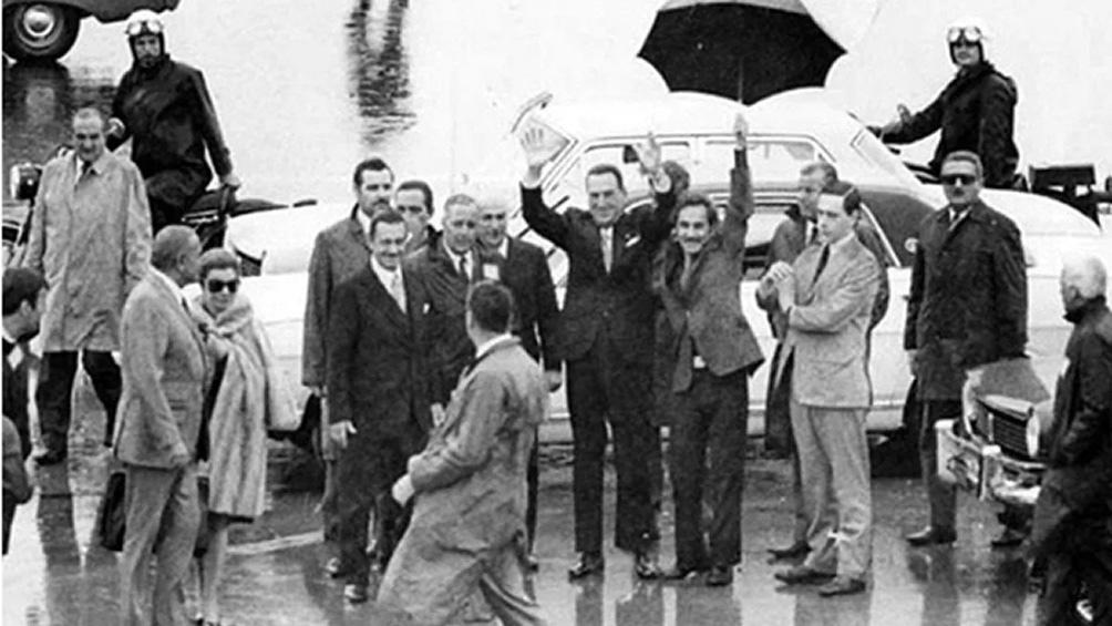José Ignacio Rucci, paraguas en mano, protegiendo de la lluvia al General