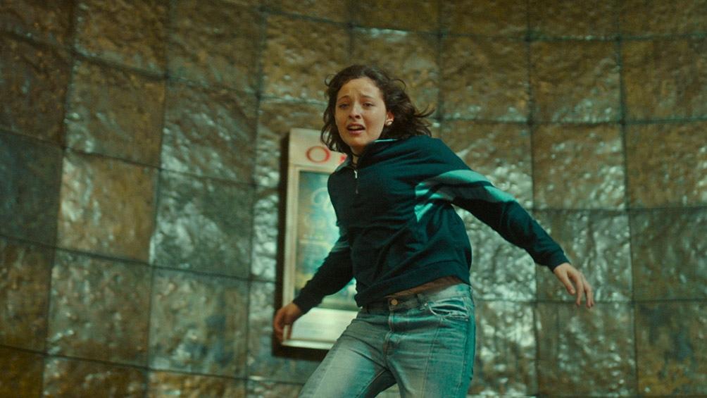 Ángela bajando las escaleras de la sala a toda prisa, buscando la salida en un lugar sin salida.