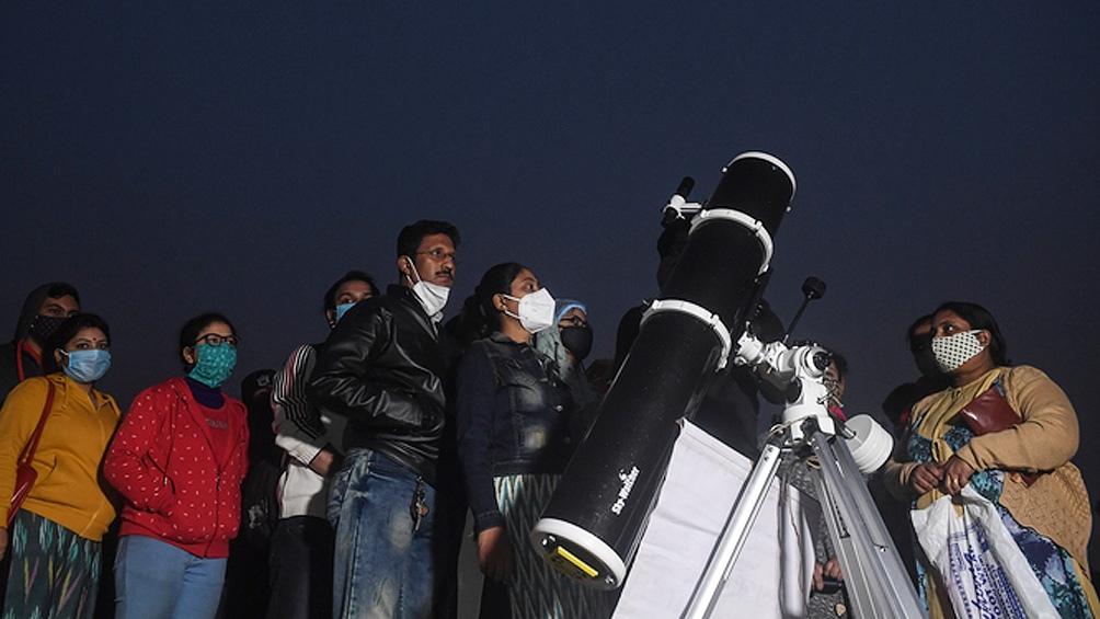 Un grupo de personas hace cola para ver la Gran conjunción en el área de Maidan, en Calcuta, India. (Foto: AFP)