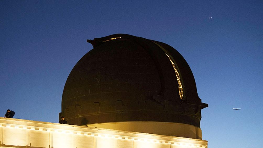 Junto a la cúpula del telescopio, la gente mira desde el techo del Observatorio Griffith, en Los Ángeles (EEUU), cómo los dos planetas llegan a su acercamiento más cercano en 400 años. (Foto: AFP)