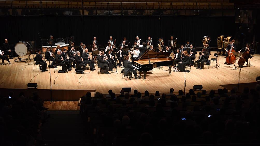 La obra, con letra y supervisión coral del argentino Luciano Bibiloni (platense también afincado en Francia) y de Hélène Hucher y Egor Lisitsyn, suma la presencia de la Banda Sinfónica Nacional de Ciegos