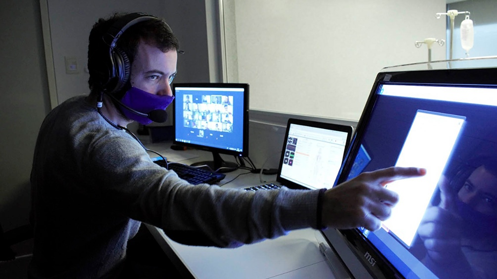 El alumno, desde una computadora, accede al software del centro e interacciona en primera persona con un paciente y colegas como si estuviesen dentro de un escenario de simulación.