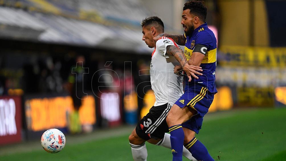 Angileri y Tevez disputan la pelota.
