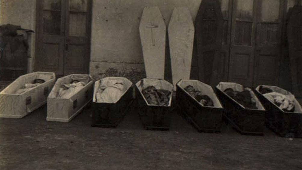 Siete de los ocho féretros alineados en el cementerio de Azul.
