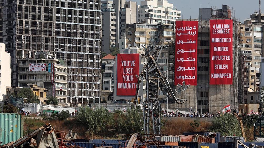Na área portuária, a mais atingida em Beirute, enormes outdoors nos poucos prédios que restam exigem o aprofundamento das investigações.  (Foto: AFP)