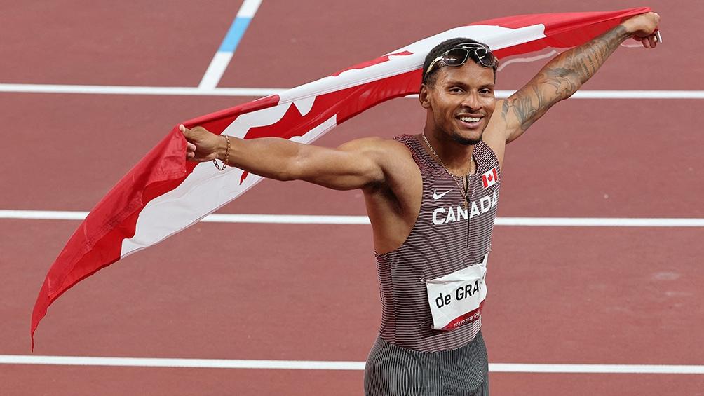 Andre De Grasse después de la gloria con la bandera de Canadá.