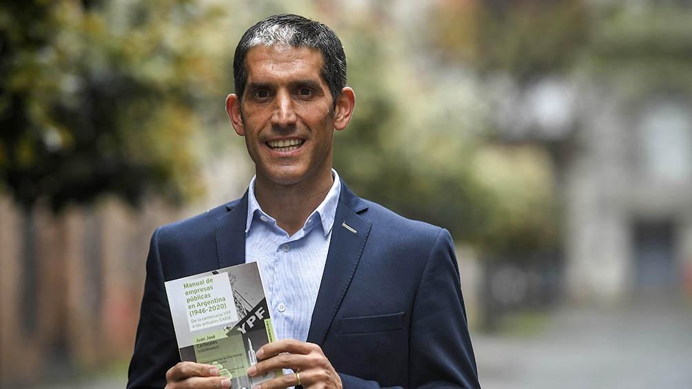 Juan José Carbajales con su obra, a la que se puede acceder de manera libre en la página de la editorial universitaria y que se comercializa a precios populares en su versión en papel.