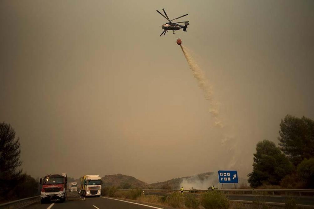 Un helicóptero arroja agua sobre las llamas en Estepona. Foto: AFP.